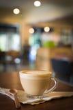 De hete Koffie van kunstlatte in een kop op houten lijst en Koffiewinkelbl Royalty-vrije Stock Foto's