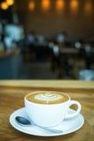 De hete Koffie van kunstlatte in een kop op houten lijst en Koffiewinkelbl Stock Foto