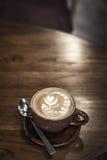 De hete Koffie van kunstlatte in een kop op houten lijst en Koffiewinkelbl Stock Afbeeldingen