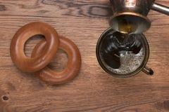 De hete koffie wordt gegoten van een Turkse koffiepot in een kop, zijn de handen zichtbaar Stock Afbeelding