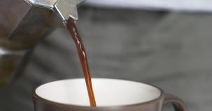 De hete koffie wordt gegoten van mokacoffeemaker stock videobeelden