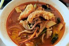 De hete kruidige Chinese soep met noedels en de zeevruchten dienden met gebraden pijlinktvis bij een beroemd restaurant in de Sta royalty-vrije stock afbeelding