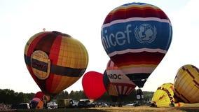 De hete luchtballon verlaat de grond en vliegt tot de bovenkant, voorbereidingen treffend te vliegen, unicef stock videobeelden