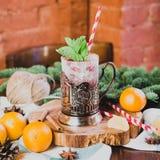 De hete overwogen wijndrank met citroen, appel, kaneel, anijsplant en andere kruiden in een glaskop tussen spar vertakt zich  Stock Fotografie