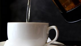 De hete thee wordt gegoten in de kop van theepot stock videobeelden