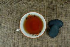 De hete theekop porselain met het ontspannen stenen op jute en bij zwarte houten achtergrond/ontspant ogenblik! Theetijd royalty-vrije stock afbeeldingen