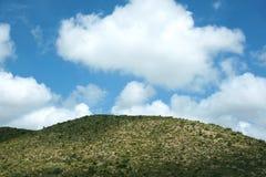 De heuvel van de woestijn en grote wolken Stock Foto