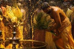 De Hindoese liefhebbers voeren het kurkuma het baden ritueel tijdens het jaarlijkse festival uit dat bij Amman tempel wordt gehou Stock Foto