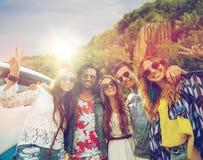 De hippievrienden bij minivan auto die vrede tonen ondertekenen Stock Foto