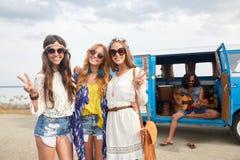 De hippievrienden dichtbij minivan auto die vrede tonen ondertekenen Stock Foto's