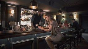 De Hipsterbarman die ingrediënten combineren en cocktails in bar maken terwijl de jongelui vrouw verstoort zit dichtbij barteller stock videobeelden