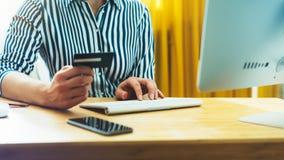 De Hipsterholding in handencreditcard, vrouwen het winkelen online aankoop, geniet van om Internet te kopen, die op kantoor met m royalty-vrije stock foto