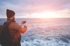 De Hipsterkerel met in blik schiet video met oceaanlandschap op mobiele telefoon Royalty-vrije Stock Foto