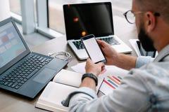 De Hipstermens zit in koffie, gebruikt smartphone, werkt aan twee laptops De zakenman leest een informatiebericht in telefoon royalty-vrije stock afbeelding