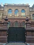 De historische bouw met ornamenten en omheining met smeedijzerpoorten stock afbeelding