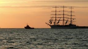 De historische lange schoener van de schipreplica drijft op zee voorbij de vuurtoren dichtbij een kleinere slepende boot stock videobeelden