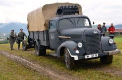 De historische vrachtwagen met twee mensen kleedde in Duitse nazi uniformen tijdens het historische weer invoeren van Wereldoorlo Royalty-vrije Stock Foto's