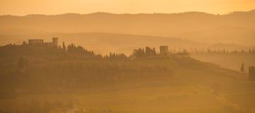 De historiska husen på kullarna av Tuscany under soluppgången arkivbild