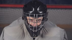 De hockeykeeper draagt een helm en heft zijn hand op die de scheidsrechter aantonen dat hij klaar is stock videobeelden