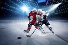 De hockeyspelers schiet de puck en de aanvallen