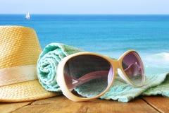 De hoed en de zonnebril van Fedora over houten lijst Stock Afbeeldingen