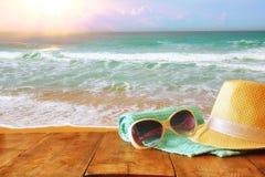 De hoed en de zonnebril van Fedora over houten lijst en overzees Stock Fotografie