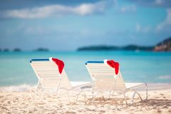 De hoed van close-upsanta op stoel op tropisch wit strand stock afbeeldingen