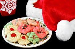 De hoed van de kerstman naast een plaat van koekjes en een mok. Stock Afbeelding