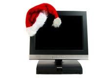 De hoed van de kerstman op een bureaucomputer stock afbeelding
