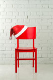 De Hoed van de kerstman op een stoel Stock Afbeelding