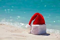De hoed van de kerstman is op een strand Stock Foto