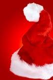 De hoed van de kerstman op rode achtergrond Stock Afbeeldingen