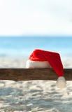 De hoed van de rode Kerstman op houten bank op het strand Royalty-vrije Stock Fotografie