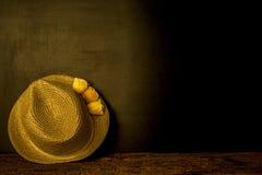 De hoed van het meisjesstro op donkere achtergrond Royalty-vrije Stock Foto's