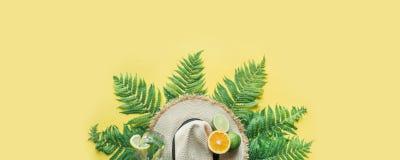 De hoed van het strandstro, varenbladeren en citrics op gele achtergrond Ruimte voor tekst Het concept van de zomer banner stock foto