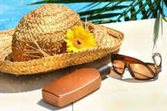 De hoed van het stro, glazen en zonnebrandolie stock fotografie