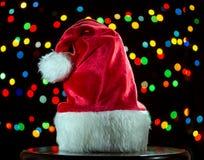 De hoed van de kerstman op de achtergrond van een verlichting stock foto