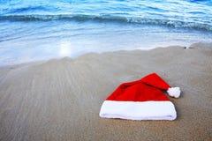 De hoed van de Kerstman op Caraïbisch strand De achtergrond van Kerstmis stock foto