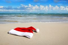 De hoed van de Kerstman op Caraïbisch strand De achtergrond van Kerstmis stock afbeelding