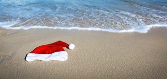 De hoed van de Kerstman op Caraïbisch strand De achtergrond van Kerstmis stock fotografie