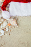 De Hoed van Kerstmis op het Strand Kerstman het zand dichtbij shells vakantie Nieuwe jaarvakantie De ruimte van het exemplaar Kad Stock Afbeeldingen