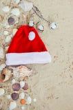 De Hoed van Kerstmis op het Strand Kerstman het zand dichtbij shells vakantie Nieuwe jaarvakantie De ruimte van het exemplaar Kad Stock Fotografie