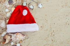 De Hoed van Kerstmis op het Strand Kerstman het zand dichtbij shells vakantie Nieuwe jaarvakantie De ruimte van het exemplaar Kad Royalty-vrije Stock Afbeeldingen
