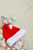 De Hoed van Kerstmis op het Strand Kerstman het zand dichtbij shells vakantie Nieuwe jaarvakantie De ruimte van het exemplaar Kad Stock Afbeelding