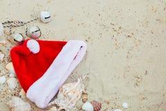 De Hoed van Kerstmis op het Strand Kerstman het zand dichtbij shells vakantie Nieuwe jaarvakantie De ruimte van het exemplaar Kad Stock Foto's