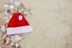 De Hoed van Kerstmis op het Strand Kerstman het zand dichtbij shells vakantie Nieuwe jaarvakantie De ruimte van het exemplaar Kad Stock Foto
