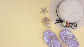 De hoed van de witte vrouw en pantoffels en shells op de gele achtergrond - houd motie tegen stock video