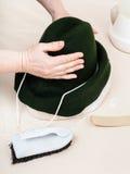 De hoedenmaker bevestigt een gevoelde kap op model voor het vormen Stock Afbeeldingen