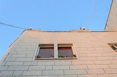 De hoek van een nieuwe woningbouw met een venster op een blauwe hemelachtergrond Stock Foto