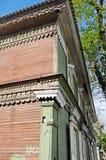 De hoek van oud houten two-storey huis met venster blinden en het snijden Stock Afbeeldingen